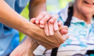 a home care allied health support worker holds elderly patients hand