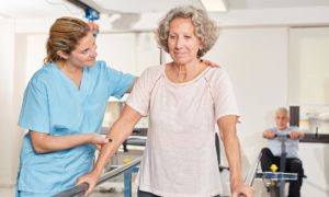 Allied health staff member helping an aged care resident with rehabilitation