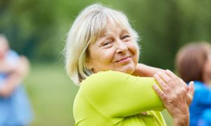 Wellness and prevention allied health for aged care approach with a senior woman stretching